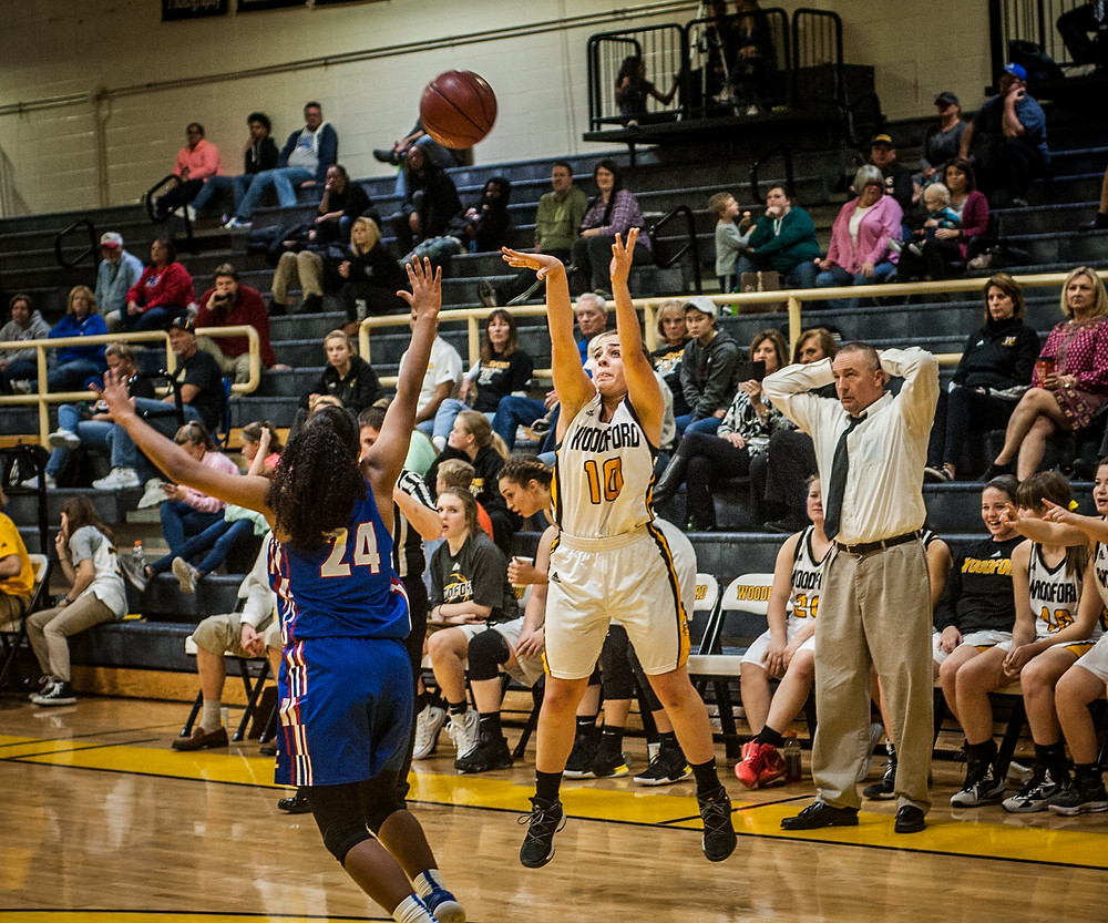 SENIOR PEYTON ROSE launches a three-pointer as Coach Steve Jaco looks on. The Lady Jackets won the game against Montgomery County on Nov. 28 by a score of 62-23. (Photo by Bill Caine)