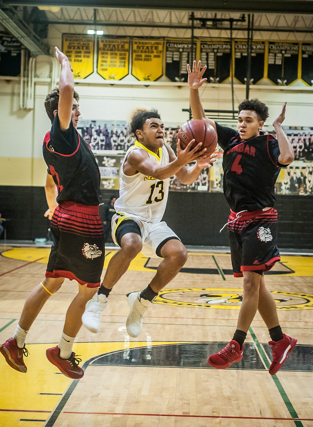 SOPHOMORE ANTHONY TABOR jumps between a pair of Dunbar defenders to attempt a layup in the season opener on Monday, Nov. 27 at Woodford County High School. (Photo by Bill Caine)