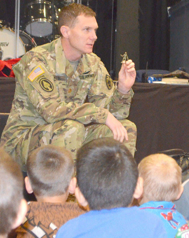 """A TOY SOLDIER, like this one held by Army National Guardsman Stephen Martin, was given to every student at Woodford Christian School as a reminder """"to pray for veterans and active military,"""" Principal Cara Meadows said. (Photo by Bob Vlach)"""