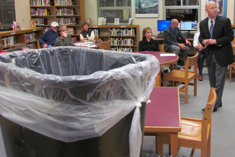 WHILE WASTE CANS collected water dripping from the Woodford County High School library ceiling, Woodford Schools Superintendent Scott Hawkins looked to a Powerpoint display while making another pitch for a new high school – and the property tax hike to pay for it. (Photo by John McGary)