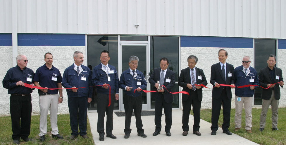 "TOP OFFICIALS OF the AHK Textiles, Ltd., cut the ribbon at Wednesday's grand opening outside the company's 91,000 square foot facility at Midway Station called ""AHK Georgetown."" The plant manager said 70 people work there presently, with another 13 expected to be hired by the time the company begins mass production of headliners for Toyota in late August. (Photo by John McGary)"