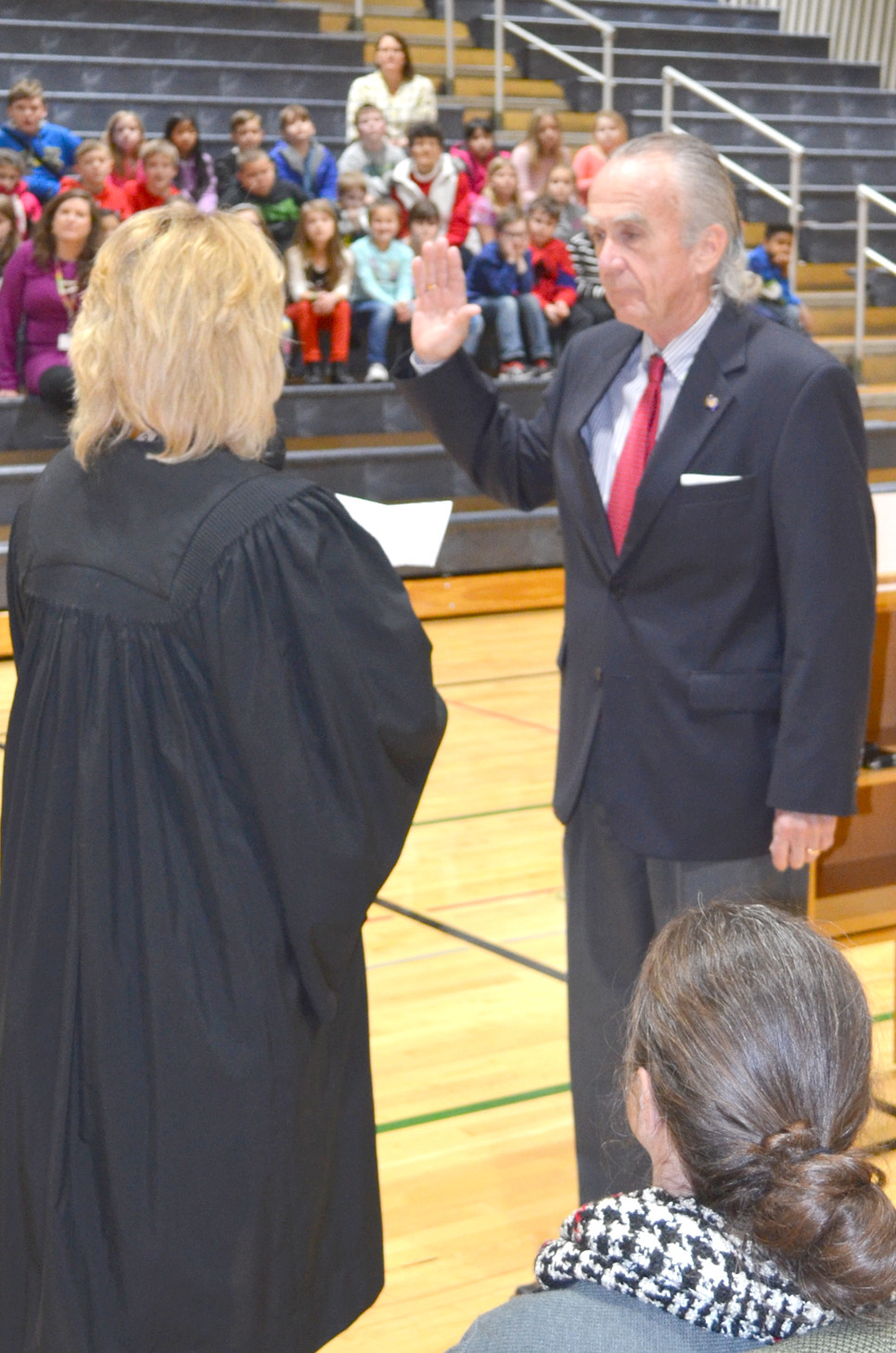 AMBROSE WILSON IV, who has served on the Woodford County Board of Education for over two decades, was sworn-in for another four-year term on Monday afternoon, Jan. 9 at Northside Elementary School in Midway. Woodford District Judge Mary Jane Phelps administered the oath of office at a ceremony attended by third-, fourth- and fifth-graders. (Photo by Bob Vlach)