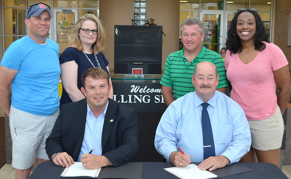JULY HAS BEEN PROCLAIMED Park and Recreation Month in Versailles and Woodford County. Joining Mayor Brian Traugott, seated at left, and Judge-Executive John Coyle for the proclamation signing at Falling Springs Arts and Recreation Center were parks and recreation staffers, from left, standing, custodian Chad Bivona, accounting manager Heather Major, executive director Rich Pictor and assistant director Chanté Bowman. (Photo by Bob Vlach)