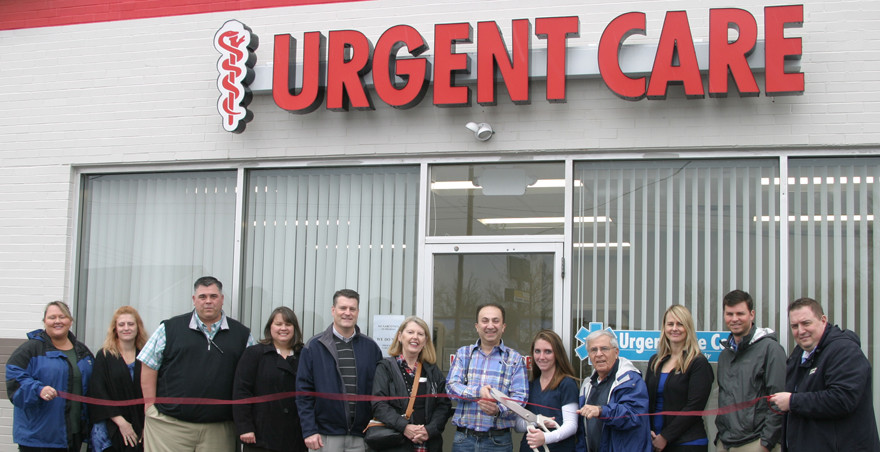 VERSAILLES URGENT CARE held a ribbon-cutting Monday to celebrate the Jan. 23 opening of its clinic at 432 Lexington Road. Holding the ceremonial big scissors is office manager Kayla Kennedy; to her right is Dr. Nawar Soda, the co-owner of the clinic. They are joined by members of the Woodford Chamber of Commerce. (Photo by John McGary)
