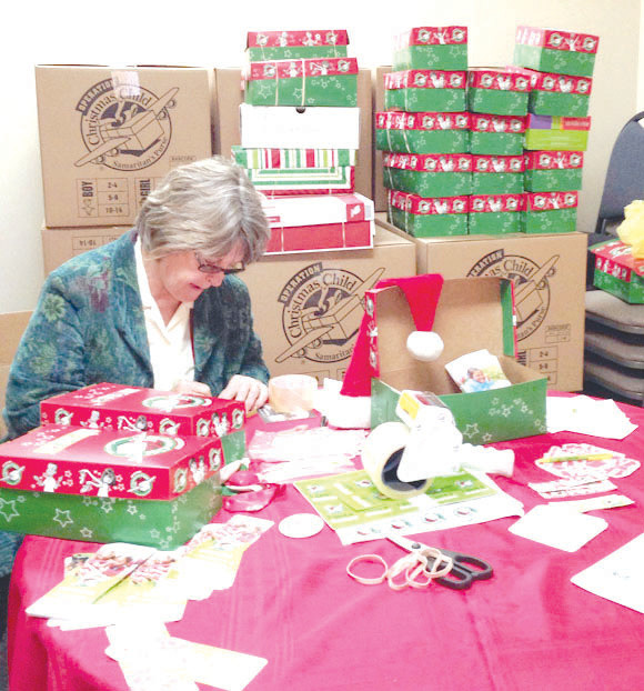 OPERATION CHRISTMAS Child shoebox gifts were sorted by Joan Mazuruk and other volunteers at First Christian Church last November. This year's collection week began Monday and will continue through next Monday, Nov. 19, at the First Christian Church Life Center, 160 Lexington Street in Versailles. (Photo submitted)