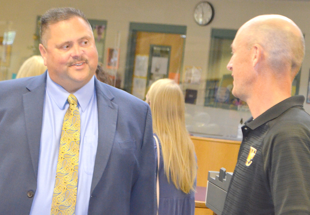 DANNY ADKINS, left, talked to Southside Elementary School Principal Jeremy Reynolds prior to being introduced as Woodford County Public Schools' next superintendent. He will succeed Scott Hawkins, who's retiring from the post at the end of this month. (Photo by Bob Vlach)