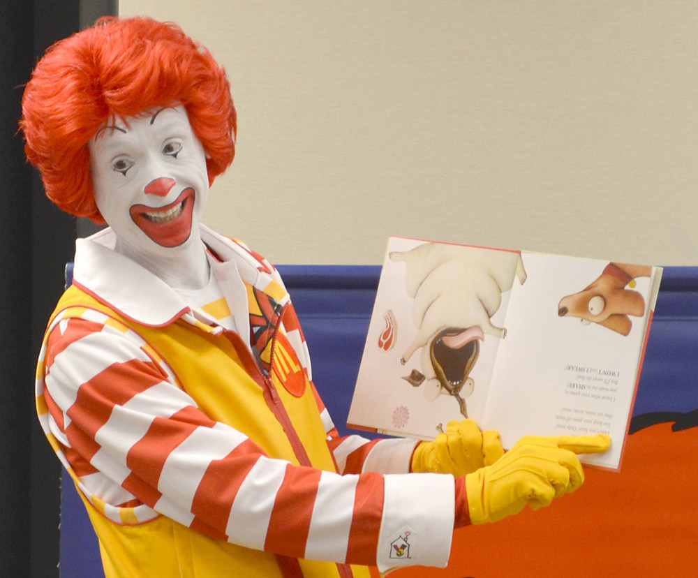 """RONALD MCDONALD eventually realized a book he was reading had been turned upside down, but not before his audience's laughter filled the Woodford County Library's community room. """"I thought it was in French,"""" he tells the children gathered around him. (Photo by Bob Vlach)"""