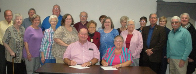 Woodford County Judge-Executive John Coyle (left) and Kathy Cole (right), president of the Woodford County Retired Teachers, recently signed a proclamation for the week of Oct. 14 as Kentucky Retired Teachers Week, as members looked on. (Photo submitted)