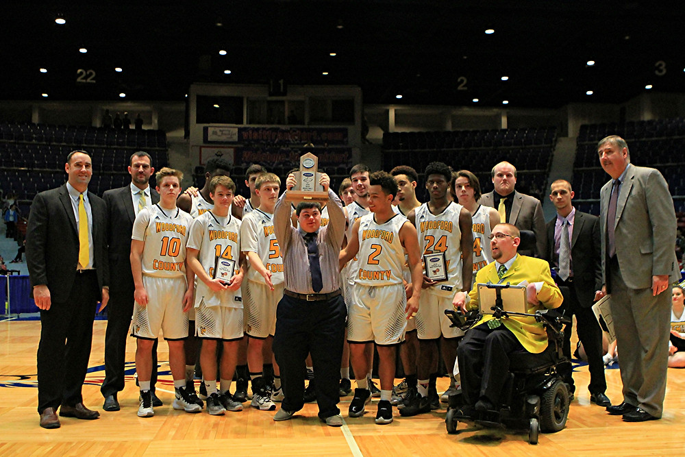 MATTHEW HEIGLE, team manager of the Woodford County High School boys' basketball team, proudly stands with his teammates and holds up the second-place trophy that the Yellow Jackets earned following their 65-57 loss to Franklin County in the championship game of the 41st District Tournament at the Frankfort Civic Center on Friday, Feb. 26. (Photo by Steve Blake/multiexposures.com)