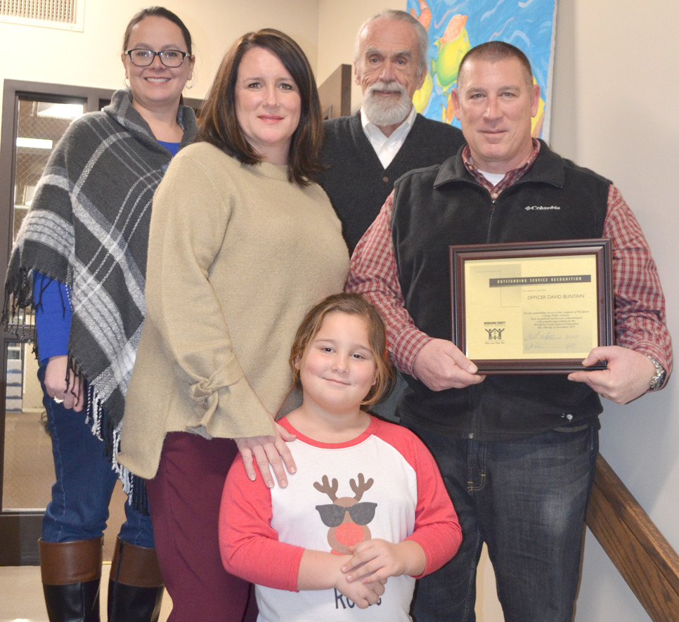 "OFFICER DAVID BUNTAIN was thanked for his nine years of ""outstanding service"" as Woodford County Middle School's school resource officer. The retired Versailles Police officer is pictured with his wife, Jennifer, and 6-year-old daughter, Reece. Woodford County Board of Education members Dani Bradley, back, left, and Ambrose Wilson IV are also pictured. (Photo by Bob Vlach)"