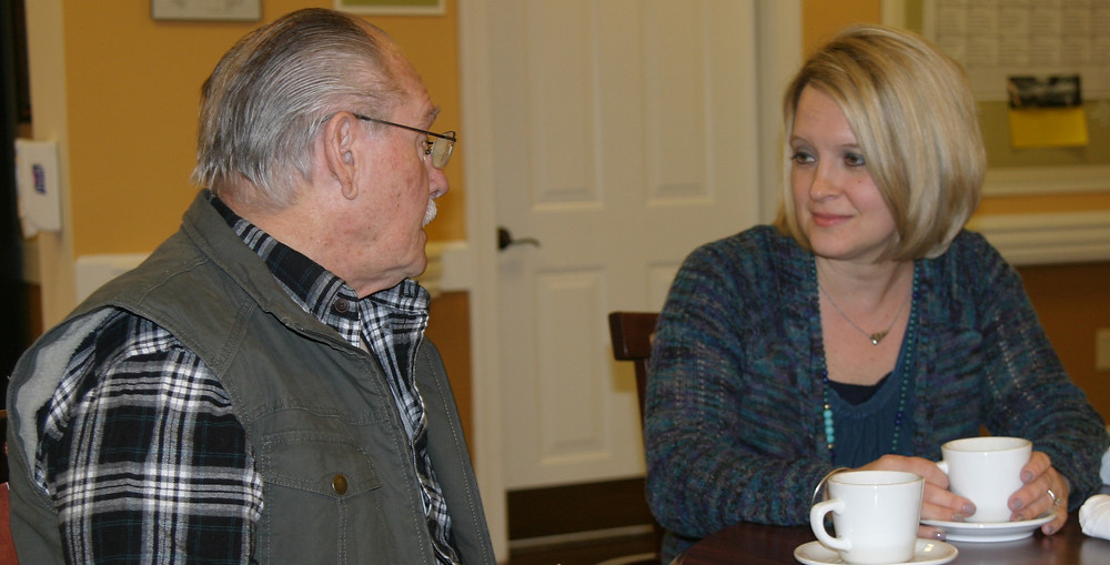 LAURIE DOROUGH, who was named executive director of Daisy Hill Senior Living last month, sits down for a cup of coffee with resident Ted Collins. Dorough says she loves spending time with the residents of the assisted living community. (Photo by John McGary)