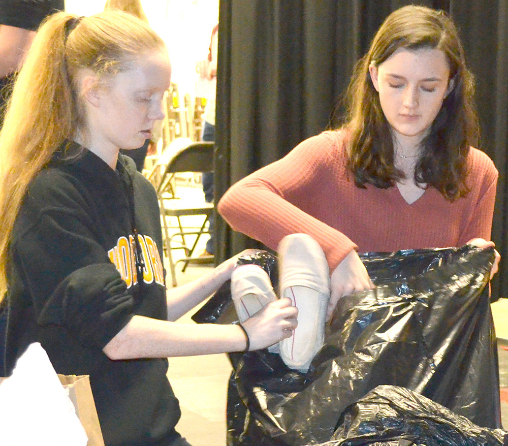 Y-CLUB MEMBERS Ginny Gregory, left, and Olivia Raybourne placed donated pairs of shoes in a large trash bag at Woodford County High School on Monday afternoon, Feb. 6. The 1,428 pairs of shoes, which were donated during a one-week shoe drive at Woodford County High School, will generate dollars for a clean drinking-water project in a third-world country. (Photo by Bob Vlach)