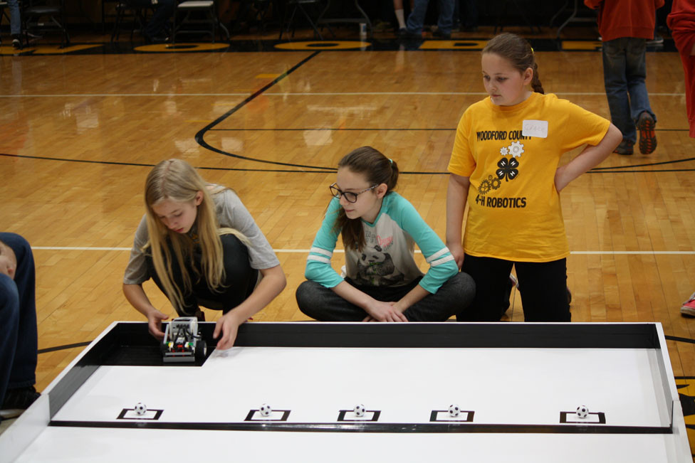 Nora Hanley, Addie Patterson and Grace Pitchford prepare their Lego EV3 Robot for the Soccer Challenge during the 2018 District 4 4-H Lego Robotics Challenge on Saturday, April 21, at the Woodford County Middle School. (Photo submitted)