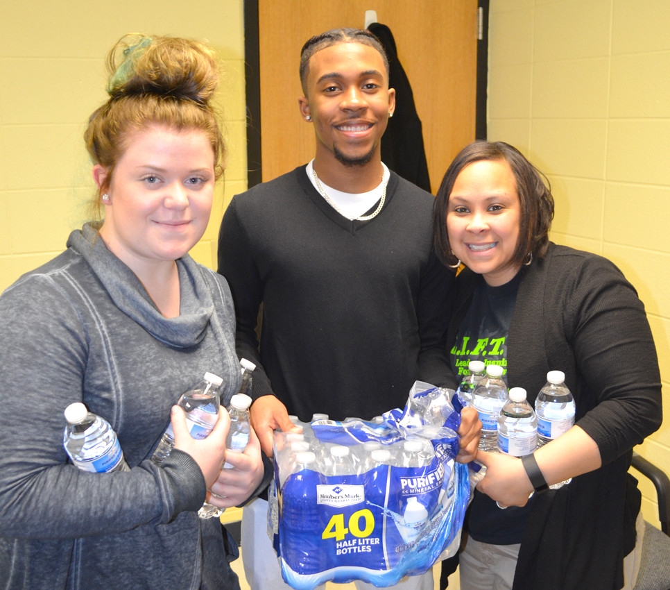 BAILEE DAMRON and Dwayne Depp, who are actively involved with the L.I.F.T. tutoring program, have joined Kristen Wilson, a guidance counselor at Woodford County High School, to support a local effort to collect bottled drinking water donations from people in the community to help residents of Flint, Mich. (Photo by Bob Vlach)