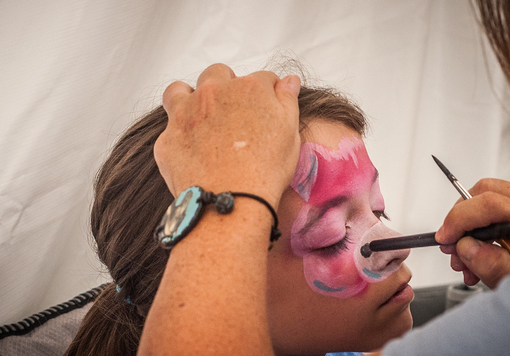 JESSIE WALTON of Versailles gets her face painted at the Midway Fall Festival. The Huntertown Elementary student is a first-timer at the festival but said she would like to come back. (Photo by Bill Caine)