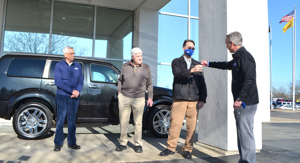 MICHAEL McINTOSH accepted the keys to an SUV from Bob Kain, general manager of Jack Kain Ford in Versailles. The Kain family donated the car to McIntosh and his fiancé, Emily Saderholm, so they'll have reliable transportation to Indiana University Medical Center, where she will get a liver transplant. From left are Pat Kain, Jack Kain, McIntosh and Bob Kain. (Photo by Bob Vlach)