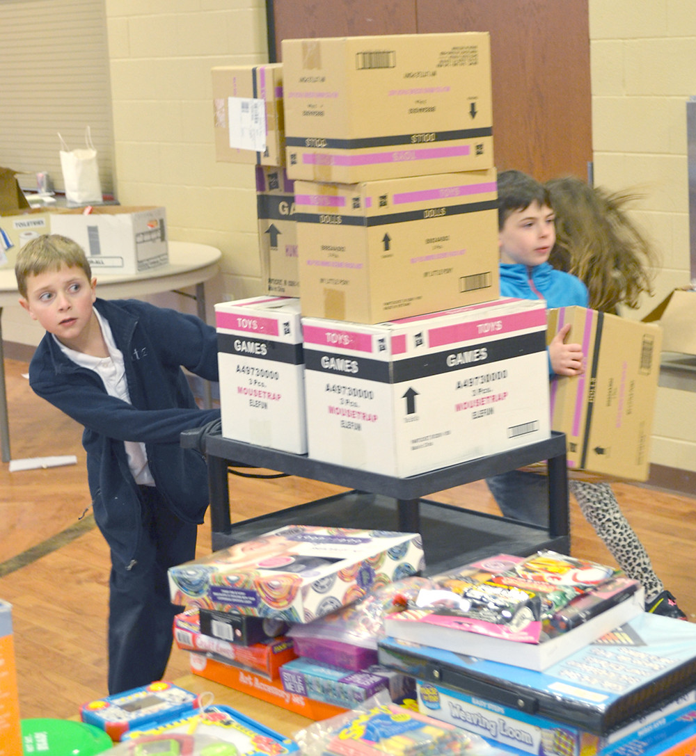 WILL SEITZ, a fourth-grader at St. Leo School, took a look around boxes stacked on a cart while helping to sort toys and other donated items for this year's Christmas Store last week. Landon Yost, another fourth-grader, is also pictured. (Photo by Bob Vlach)