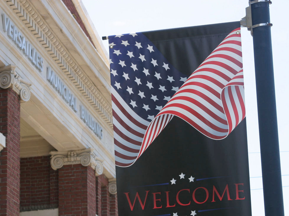 BANNER OR FLAG BANNER? A citizen upset about these banners on Main and Lexington Streets and Versailles Mayor Brian Traugott agree on one thing: there are twice as many stripes as on a real American flag. (Photo by John McGary)