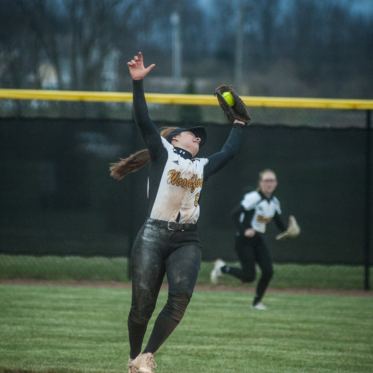 WCHS SENIOR PEYTON ROSE falls backwards after jumping to snag a line drive in the Lady Jackets win over Oldham County. (Photo by Bill Caine)