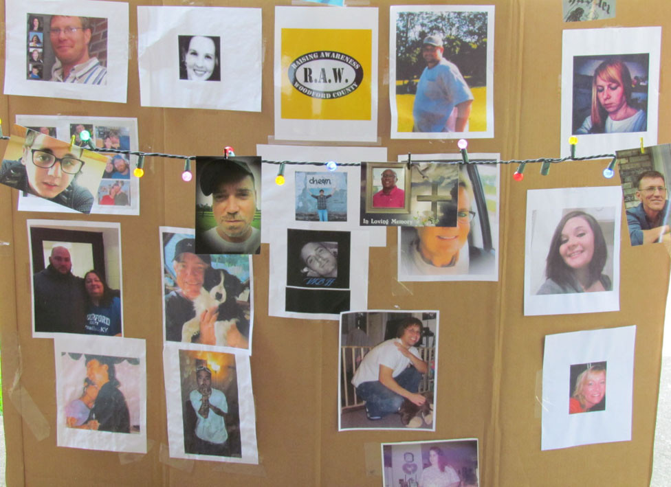 """A """"MEMORIAL WALL"""" with photos of people who died from drug overdoses was on display at RAW'S 5th annual Remembrance ceremony Sunday, Aug. 12, at Big Spring Park. Other photos were attached to three strands of Christmas lights above the board. (Photo by John McGary)"""