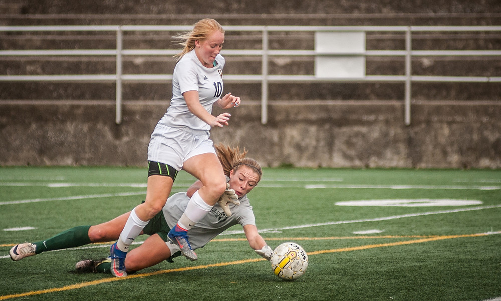 SHELBI MORRISON scores with a diving Wolverine keeper Carson Graves at her feet. (Photo by Bill Caine)