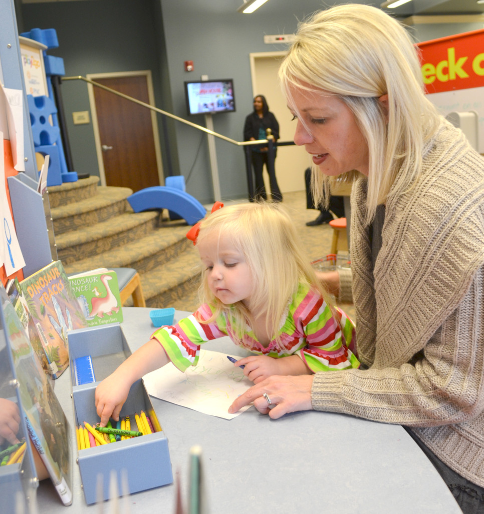 "BRINKLEY HUMSTON, 2, did some coloring with her mom, Allison, during the opening event of Science in Play 2GO at the Woodford County Library on Dec. 1. Because the Woodford County Library always has ""fun, exciting things,"" Allison Humston says she was not surprised that Versailles gets to host Science in Play 2GO's inaugural three-month residency. (Photo by Bob Vlach)"