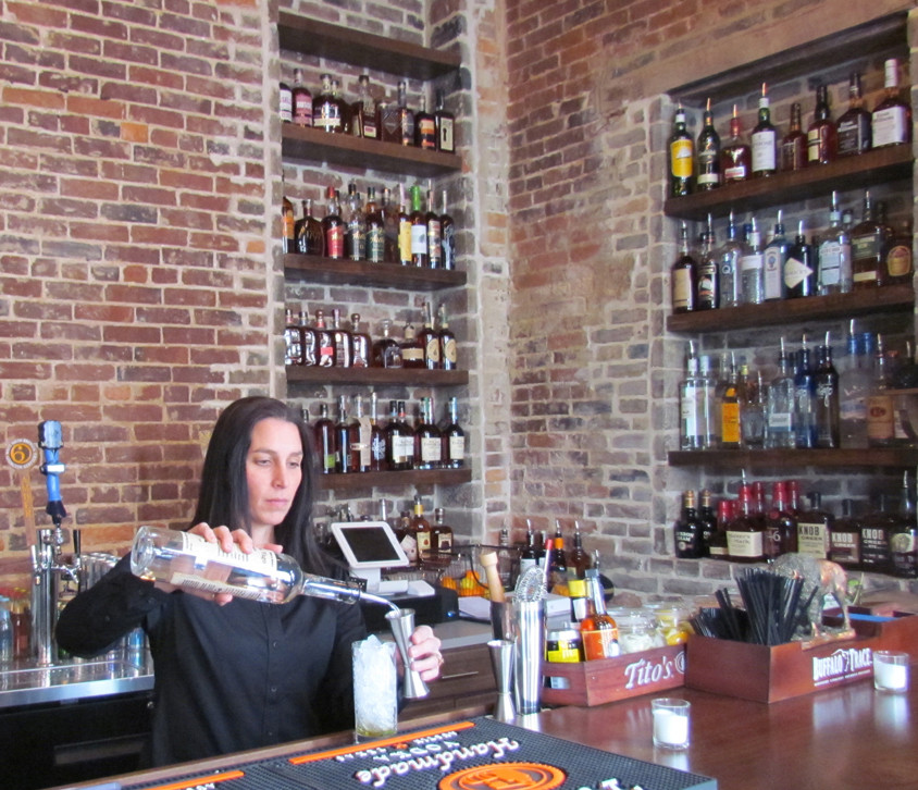 """AMSDEN BOURBON BAR manager and """"mixologist"""" Marsay Agruna said business was good when the tavern held its Feb. 8 soft opening. The small tavern has a maximum capacity of 23, with space for 10 more outside. (Photo by John McGary)"""