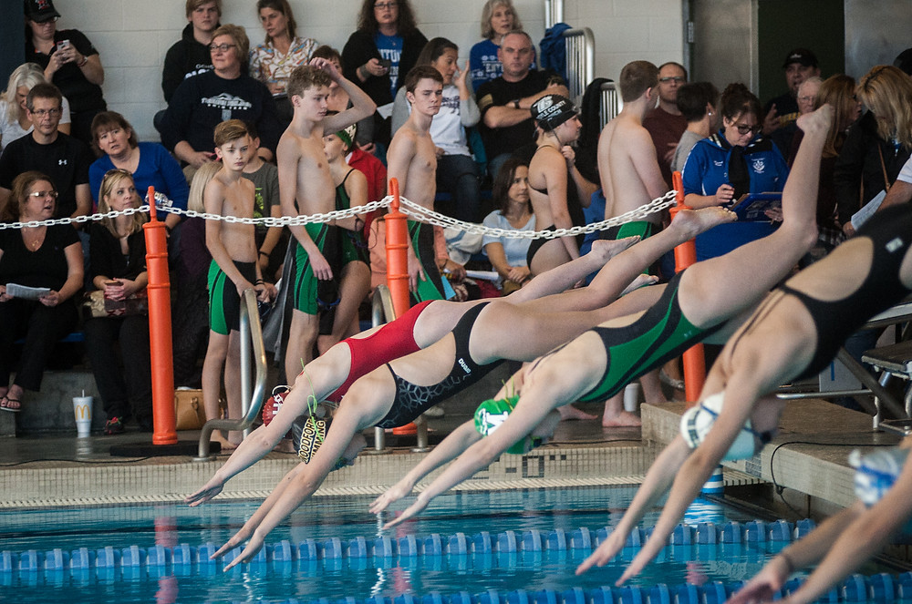 EMMA OBERLANDER ,second from the top, dives into the pool to start the women's 200-yard freestyle relay at the Woodford County Invitational on Saturday, Dec. 16. (Photo by Bill Caine)