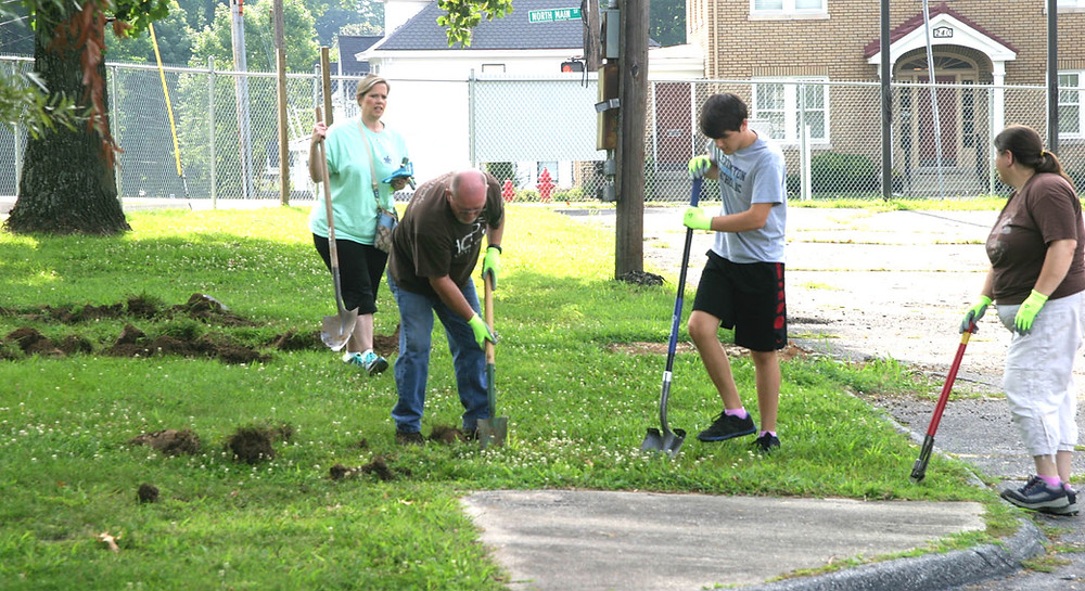 DIGGING FOR MEMORIES: From left, Melissa Wells-Strauss, James Phelps, Ethan Kesten and Sarah Kesten searched for time capsules buried on the grounds of the old St. Leo's School on Elm Street. Their two-hour dig didn't turn up anything, but they hope to return soon. (Photo by John McGary)