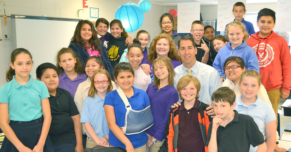 PRINCIPAL LARRY CAUDILL has been helping fifth-graders in Jennifer Page's class with their reading every morning this school year. He said every administrator and special areas teacher at Simmons Elementary was assigned a class, where they spend 45 minutes each morning supporting a school-wide focus: Literacy is the Key. (Photo by Bob Vlach)