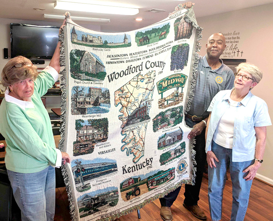 A HISTORIC TAPESTRY THROW featuring notable locales in Woodford County will be sold by the Versailles Lions Club to support its ongoing efforts to bring eye care assistance to children and adults in the community. Versailles Lions Club members Lillie Cox, left, Tim Williams and Becky Dunning are pictured with the tapestry. This committee of three led the effort to launch the fundraiser. (Photo by Guy Hollander)