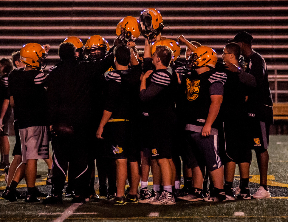 THE WOODFORD COUNTY HIGH SCHOOL football team gathers after practice for final huddle. (Photo by Bill Caine)