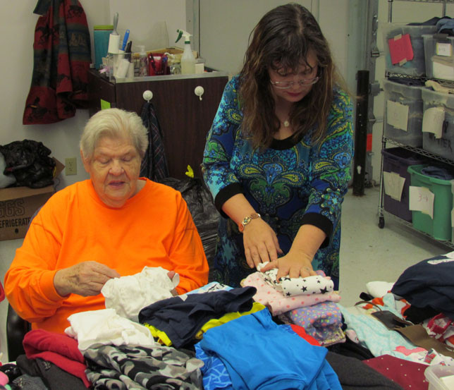 """JOURNEY PROVISIONS volunteer Marcia Crouch, left, and store director Heather Nichols, folded donated clothes in preparation for the new store's grand opening on Saturday. """"The good Lord has done a lot of things in my life, and I like to return to other people,"""" Crouch said of the 25 to 30 hours each week she volunteers at the thrift shop. (Photo by John McGary)"""