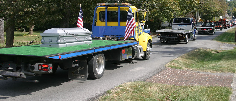 "THE TOW TRUCK carrying the casket of Eddie Hay on Friday, Oct. 6, was one of 30 or so that accompanied Hays from Versailles to a Frankfort cemetery. ""I think he's ecstatic now,"" Cory Hays said of his father, who was born in Woodford County. (Photo by John McGary)"