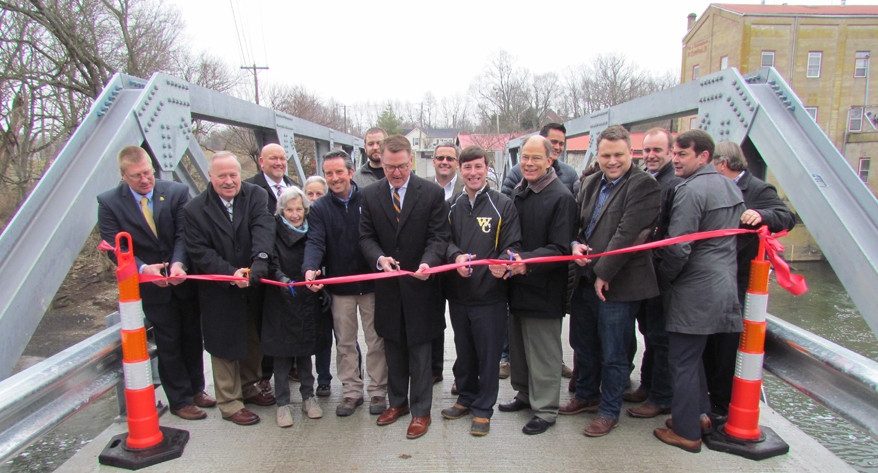 STATE TRANSPORTATION SECRETARY JIM GRAY did the honors at last Friday's ribbon-cutting ceremony on the Weisenberger Mill Bridge. The bridge reopened Dec. 23, but the ceremony was delayed to allow Gray to attend. He was joined by, to his left, Woodford Judge-Executive James Kay, state Rep. Joe Graviss and Magistrate Liles Taylor (Dist. 1) and, to his right, Weisenberger Mill owner Phil Weisenberger, and his grandmother, Better Weisenberger, who was born before the first bridge was built. (Photo by John McGary)