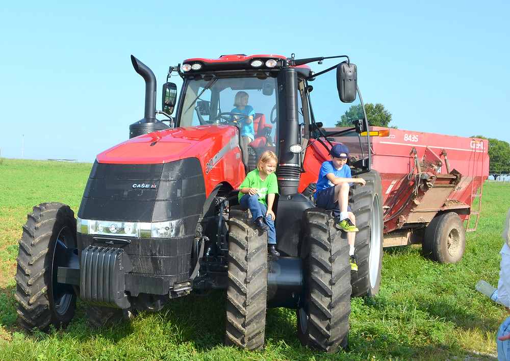 KATHERINE MACCARTHY, age 8, sat behind the steering wheel of a large tractor during a stop at the University of Kentucky's C. Oran Little Research Center during Monday's 52nd annual Woodford County Farm Tour. Also pictured are her 6-year-old sister, Madison, and Manus Lavin, 10. (Photo by Bob Vlach)