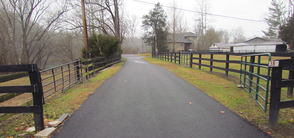 THIS GATE, about 180 feet before the end of Shryocks Ferry Road, was installed nearly eight years ago with the encouragement of the then-supervisor of the nearby Versailles Water Treatment Plant. To the left are Griers Creek and Kentucky River, which supplies water to the plant. David Dean and Sally Droste, who live just past the gate, stopped closing it in October, after complaints to county officials.                           (Photo by John McGary) (Photo is of a driveway and fences)