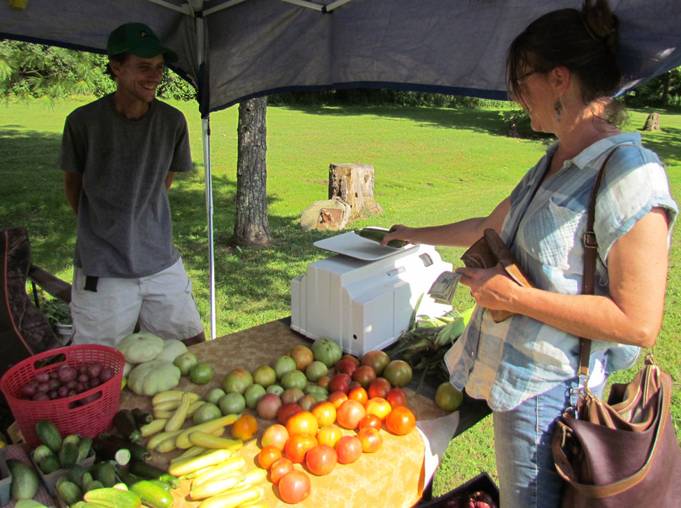 MARGIE STELZER, right, purchased zucchini from local farmer Michael Tupts at the Millville Community Market July 27. Tupts said it was his second day at the market, and business was pretty good. (Photo by John McGary)