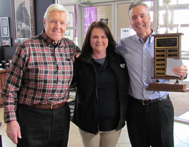 ROBBIE COTNEY, center, won the 14th annual Jack Kain Ford (JKF) Employee Chili Cook-Off Monday. Her name will be inscribed on the large trophy there. With her are Jack Kain Ford, left, and Bob Kain. Cotney said her winning ingredients included Italian sausage and her mother's special seasoning, the ingredients of which she wouldn't share. Cotney has worked at JKF for 14 months. (Photo by John McGary)