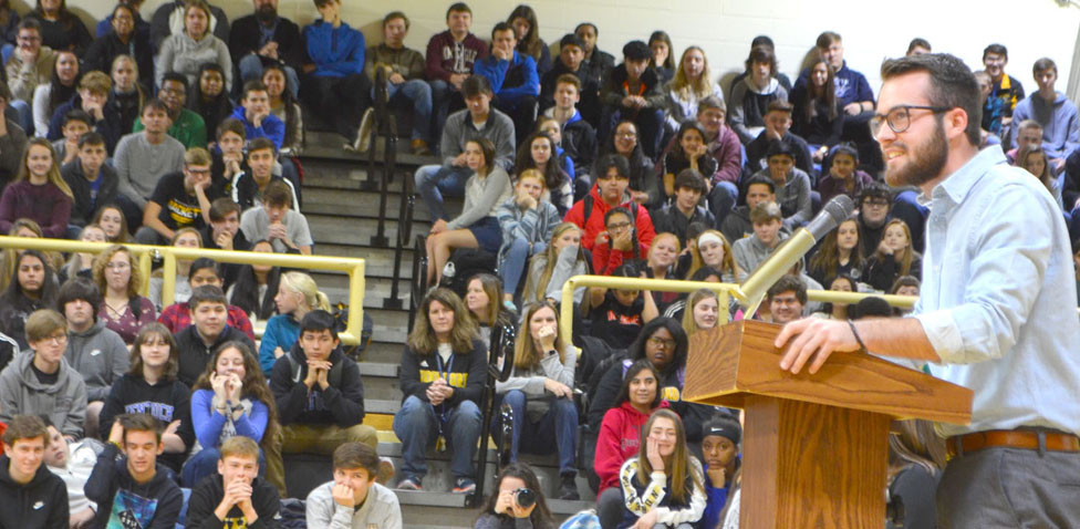 "TRISTAN FERRELL, co-executive director of Spark Community Café in Versailles and a graduate of Woodford County High School, spoke during the annual Thanksgiving Food Drive assembly at WCHS Nov. 20. Ferrell told students the food drive and Spark Café – a nonprofit pay-as-you-can restaurant – will not change the world. ""It's doing something much more important. It's changing someone's world,"" he said. (Photo by Bob Vlach)"