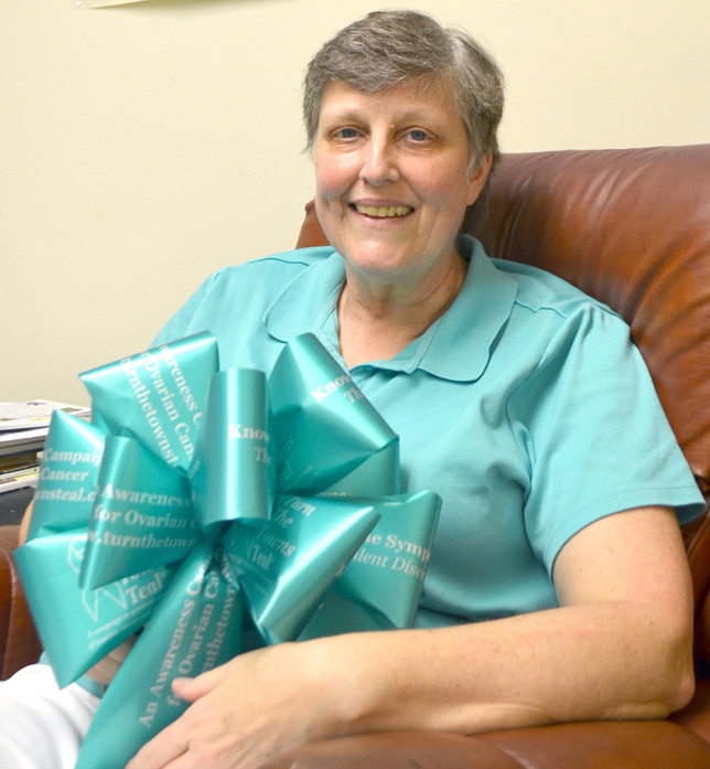 """SUE JACOBS was diagnosed with ovarian cancer before her 52nd birthday. She and other survivors are raising awareness about ovarian cancer when they """"Turn The Towns Teal"""" in September. Teal-colored bows were tied to lampposts along Main Street in downtown Versailles to remind women about being screened for this """"silent disease,"""" which has symptoms often ignored by women. (Photo by Bob Vlach)"""