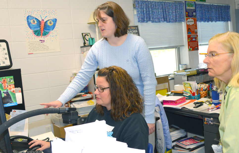 MEGHAN BOTTOM, technology integration specialist for the Woodford County Public Schools, offered assistance to Huntertown Elementary School teachers Angela Bentley, front, and Teresa Currens, far right. (Photo by Bob Vlach)