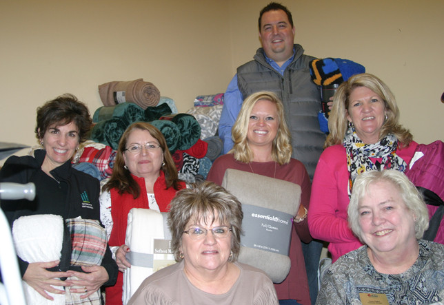SURROUNDED BY BLANKETS they helped gather, members of Leadership Woodford County prepared to distribute them to the needy. From left, first row, are Judy Beckley and Susan Hughes; second row, Lisa Johnson, Lea Martin, Julie Goodpaster and Leeann Bland. At back is Justin Carroll. (Photo by John McGary)