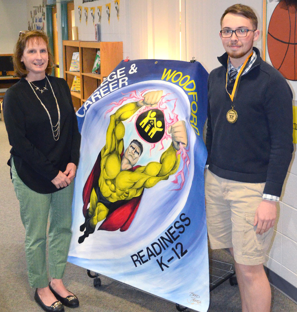 """BRAD PRARIA's """"Superheroes in Education"""" banner artwork represented Woodford County at this year's Kentucky School Boards Association (KSBA) conference in Louisville. The WCHS junior was recognized by the Board of Education on Monday. Board member Margie Cleveland is pictured with him and his art. (Photo by Bob Vlach)"""