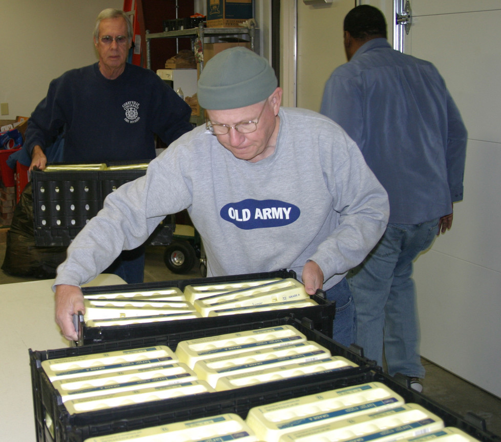 FOOD PANTRY VOLUNTEERS Jim Foster, center, Bill Phelps, left, and Fred Gudger spent a cold Tuesday morning unloading food and preparing 75 baskets of food for the needy. (Photo by John McGary)