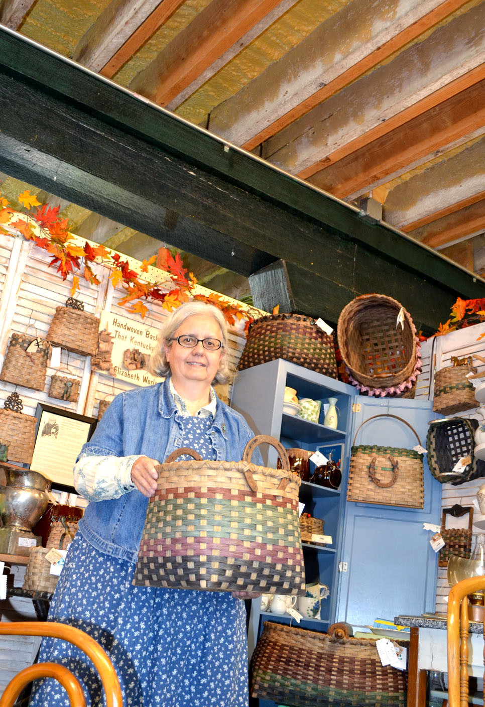 ELIZABETH WORLEY - better known as That Kentucky Lady -dips her handmade baskets in a natural walnut stain she makes herself. Worley also incorporates vintage kitchen, garden and other tools in her basket designs. She has a booth at Green Street Gifts & Antiques in downtown Versailles. (Photo by Bob Vlach)