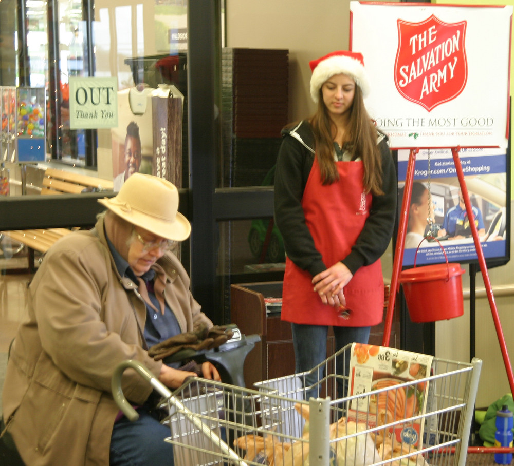 SALVATION ARMY bell ringer Stasha Hickey prepares to accept a donation from Marilyn Biles. The money donated in Woodford County stays here and helps people struggling to pay rent and utility bills – and utility bills for the Hope Ministries Food Pantry and local clothing bank. (Photo by John McGary)