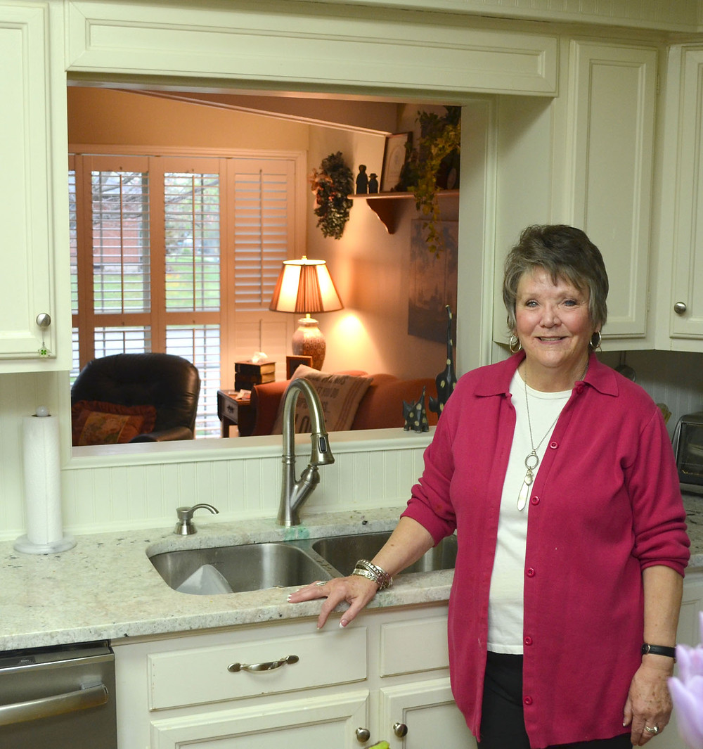CATHY NOEL had an opening cut into a kitchen wall of her Versailles home so she could see into the living room. It has been especially helpful when her grandchildren come over for a visit. (Photo by Bob Vlach)