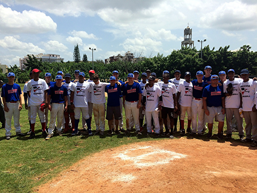 SHARED CAMARADERIE. Members of the Kentucky Rockers 17U baseball team stand with members of the Dominican Republic team they competed against in their third game of their mission trip. In the photo, the Dominican players are wearing the jerseys the Rockers' players gave them. (Photo submitted)