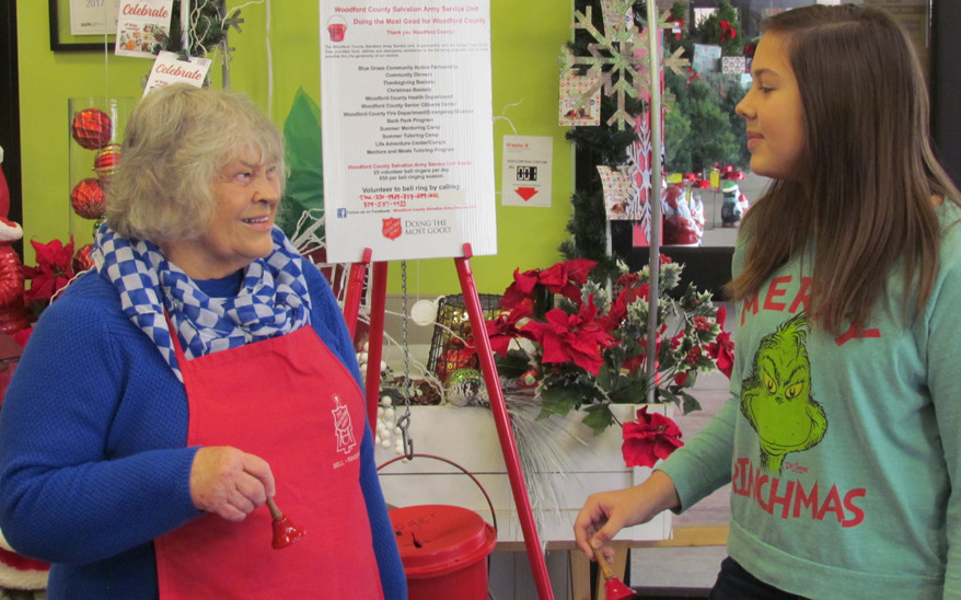 RINGING SALVATION ARMY bells is a family tradition for Patsy Shryock (left), her granddaughter Lizzy Shryock, and Lizzy's great-aunt, Peggy Carter Seal (not pictured). All the money raised in Woodford County by Salvation Army volunteers stays here. (2018 photo by John McGary)